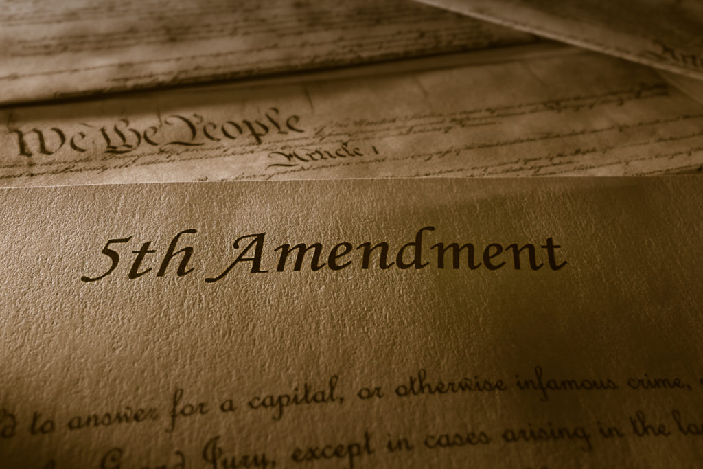 The 5th Amendment with US Constitution in the background.