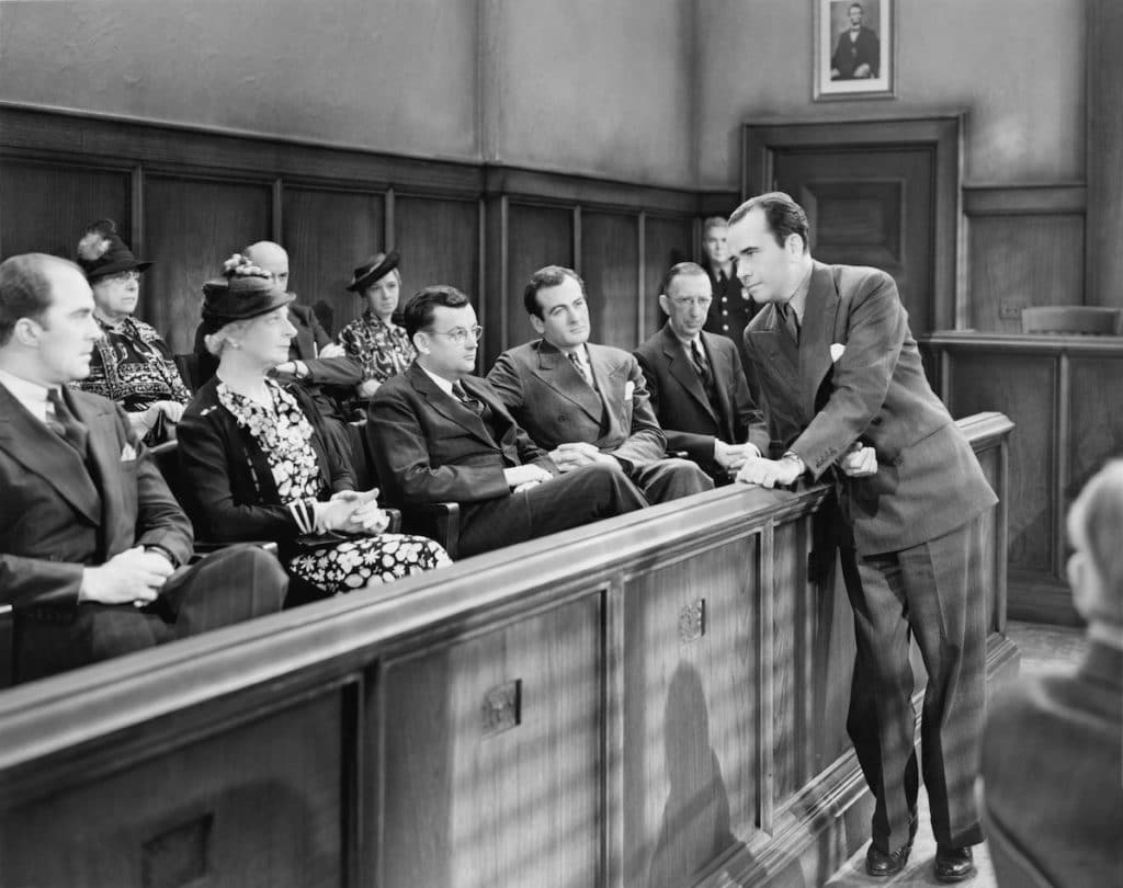 a black and white image of a jury listening to a lawyer's opening statements